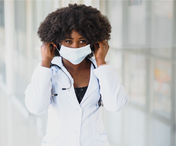 Black provider putting on a mask in clinic hallway