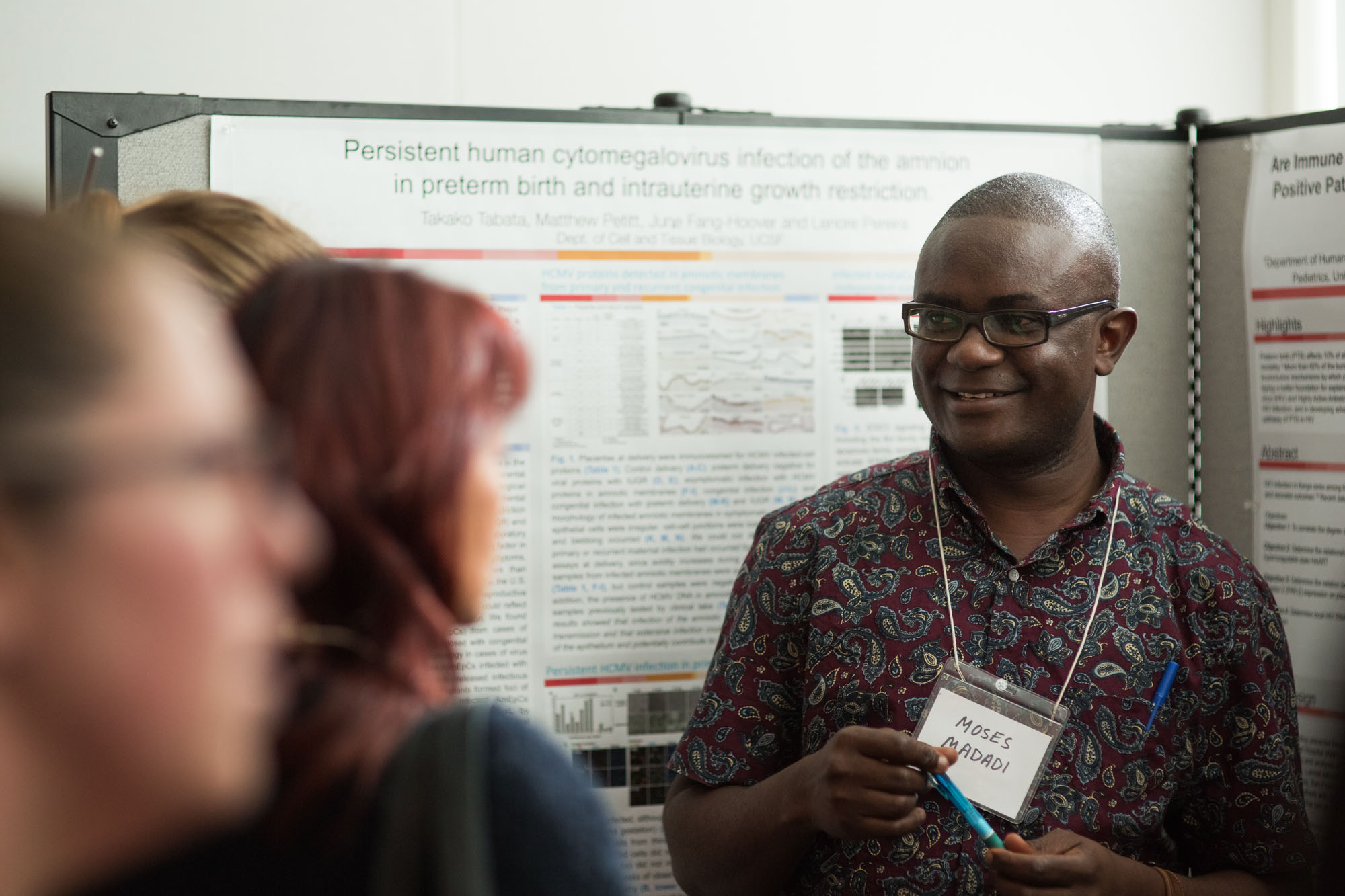 Researchers explaining his poster at the symposium poster session